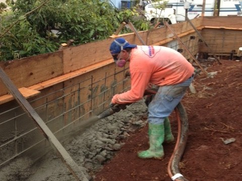 Shotcrete crew worker building a custom wall from the ground up.